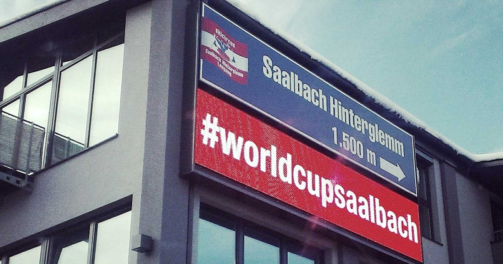 The photo shows a modern grey building with lots of windows. On one side, a large banner advertises the hashtag #WorldCupSaalbach.