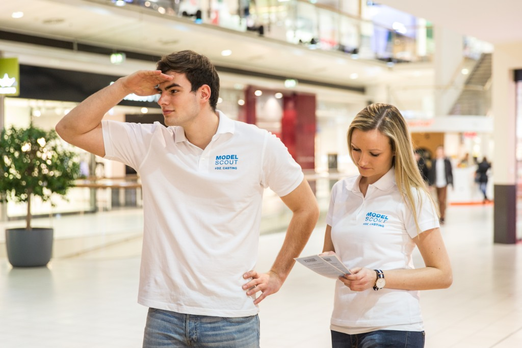 A photo of two model scouts, a man and a woman, both dressed in jeans and a white shirt branded according to the campaign. They are looking for potential models for the #dz_casting campaign at Donau Zentrum Wien.