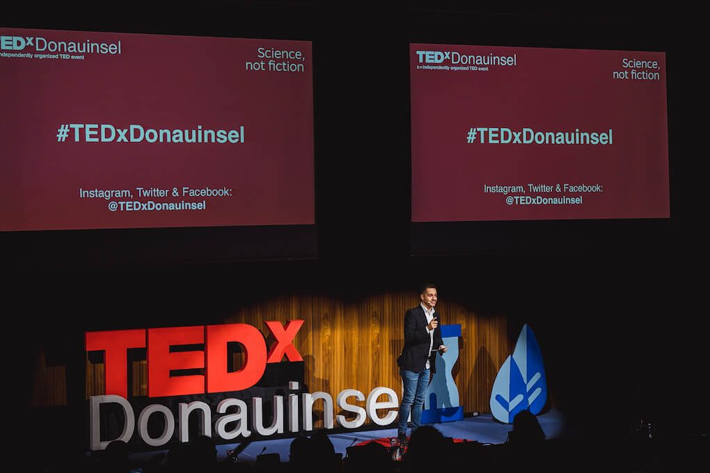 Mathias Haas with a microphone, presenting the TEDxDonauinsel 2018 event on the stage next to the big TEDxDonauinsel letters. Behind him, two projector screens advertise the event hashtag #TEDxDonauinsel and the event's Twitter, Instagram and Facebook handle @TEDxDonauinsel.