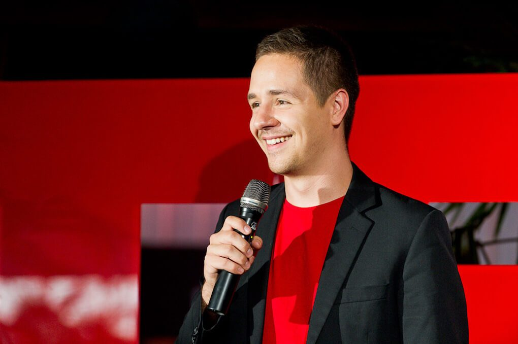 Mathias Haas wearing a TED-red t-shirt and a suit jacket, smiling and talking into a microphone on the TEDxDonauinsel stage. The T and E of the big TEDx letters can just about be seen in the background behind him.