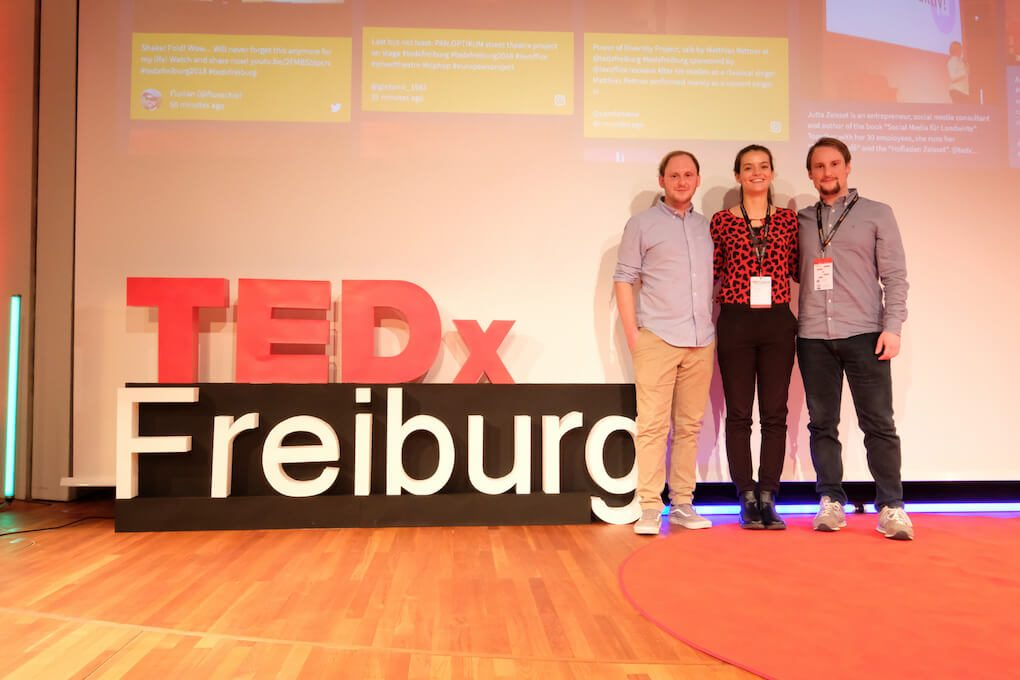 Brothers Tobias and Gabriel Brüser posing next to a large TEDx Freiburg sign with an unnamed woman between them. Behind them, parts of the large social wall displayed with Walls.io can be seen.
