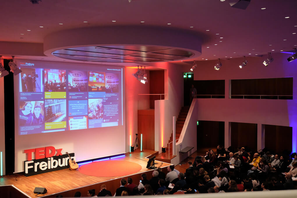 The social wall displayed on a large screen at the back of the main stage at the TEDxFreiburg event. The audience has a clear view of the stage and the projected wall.