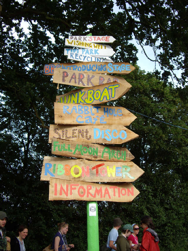 Shot of a colourful signpost from Glastonbury showing the way to various stages and areas, taken by Flickr user sachab