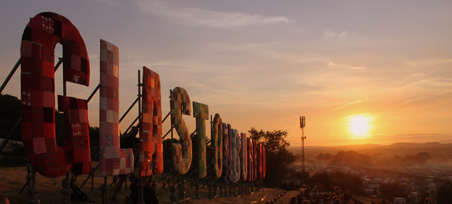 """Photo, taken by Flickr user Robbie Shade, showing the giant """"Glastonbury"""" letters in front of a stunning sunset."""