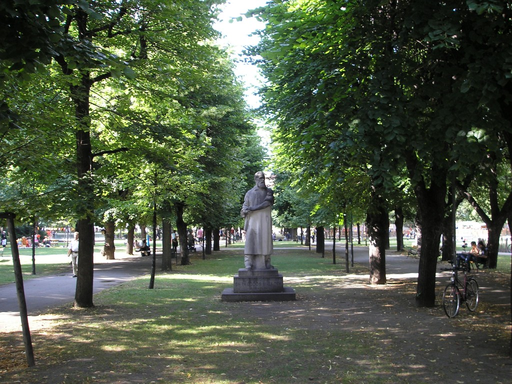 Contemporary shot of the university campus in Vienna. A statue surrounded by walkways shaded by big green trees.