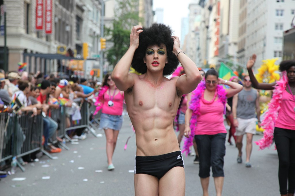 A person in black briefs and wearing a black wig and full makeup walking down the street during NYC pride in 2011.