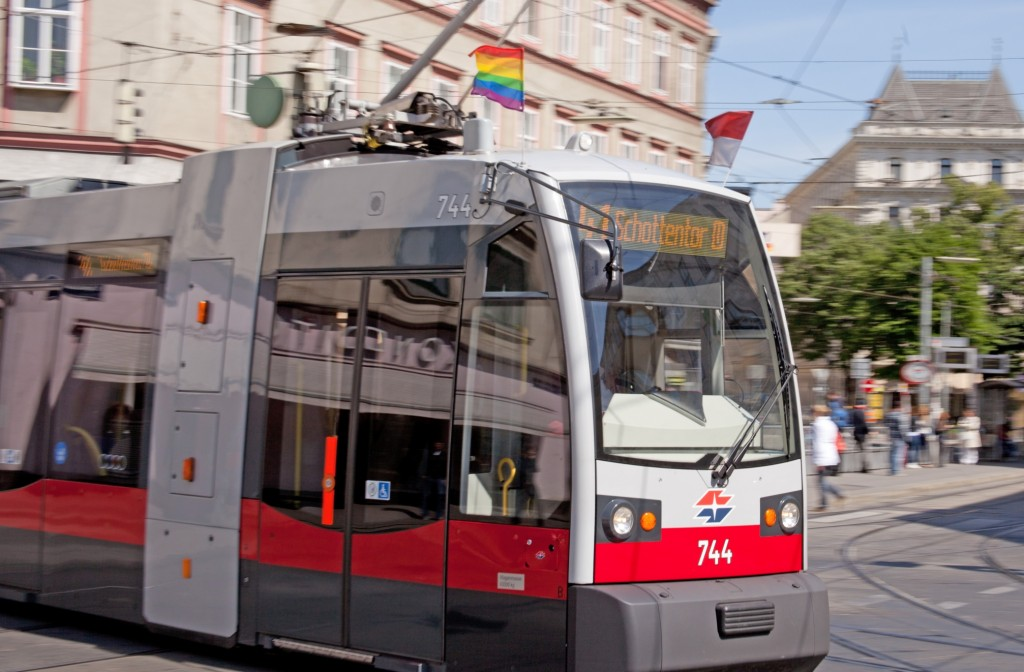 A tram in Vienna, Austria sporting a rainbow flag on its top.