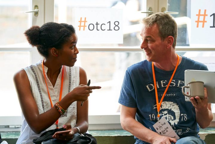 A woman and a man are engaged in a lively, friendly discussion. They're sitting in front of a glass window that has that #otc18 hashtag printed onto it.