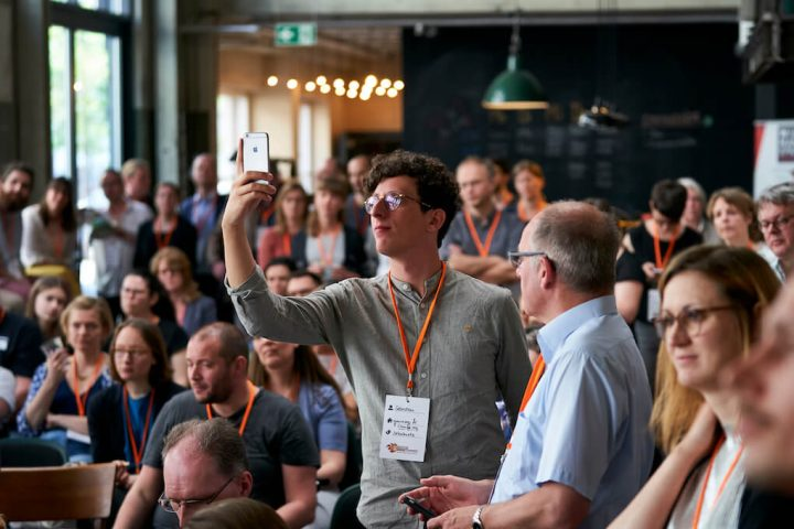 An audience member stands up to take a photo of the stage (openTransfer BarCamps)