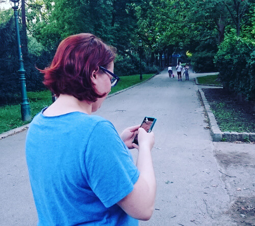Andie Katschthaler playing Pokémon Go in the park.
