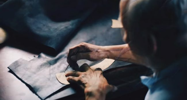 An artisan, an old man out of focus in the shot, is using a stencil to draw a shape on a piece of leather, presumably for sewing.