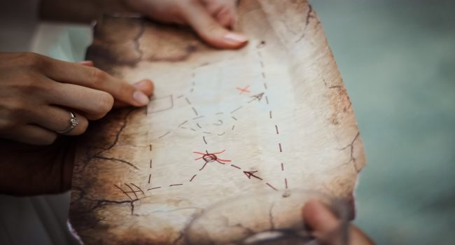 Hands holding an ancient looking treasure map, tracing the lines.