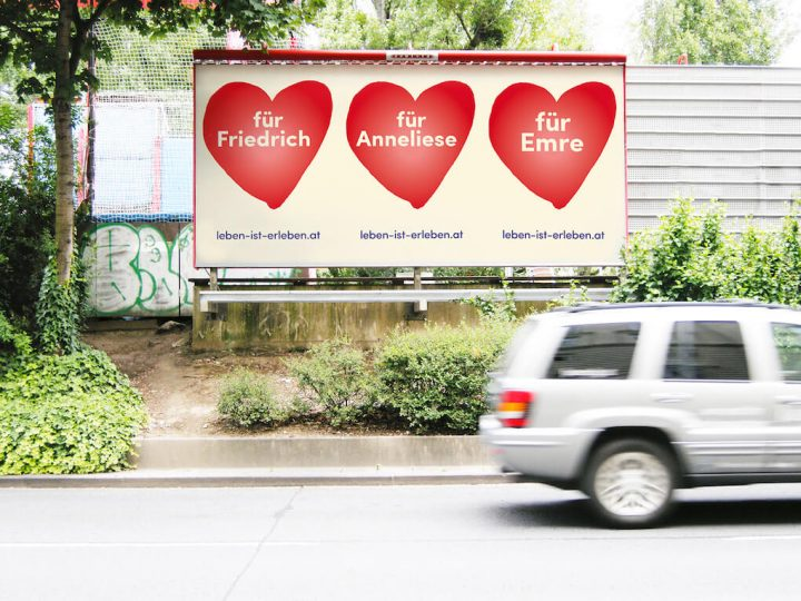 Photo of a billboard advertising the #LebenIstErleben campaign. A car drives by in the foreground.