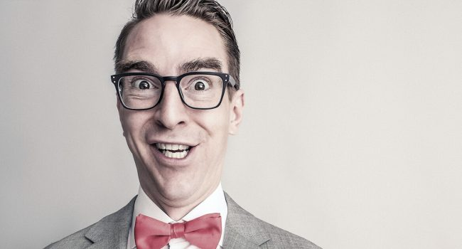 A man wearing chunky glasses and a red bow tie with a funny apprehensive facial expression.