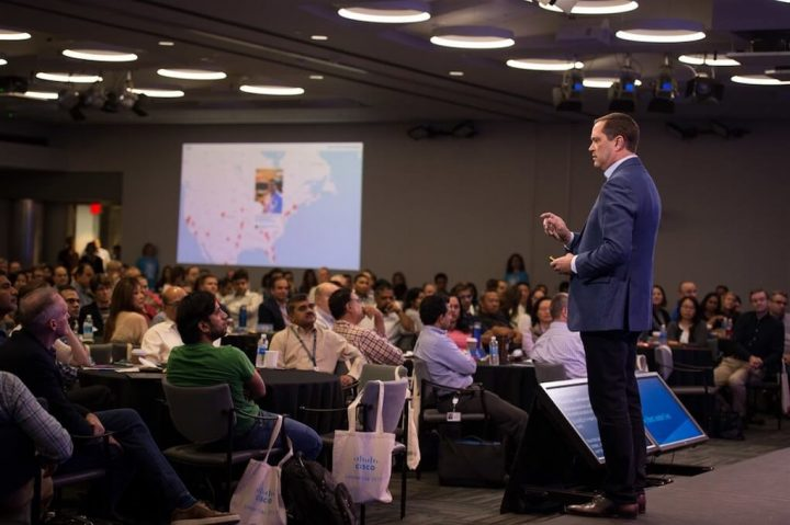 Cisco CEO Chuck Robbins speaking to a crowd. The social media wall for #CiscoLeaderDay is shown on a screen in the background.