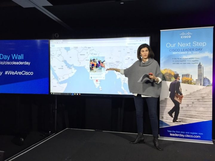 Fran Katsoudas in front of a projection of the #CiscoLeaderDay social map.