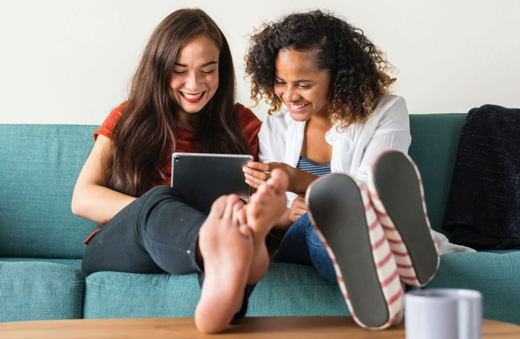 Two smiling young people sitting on a sofa, feet propped up on a coffee table. They're both looking at a tablet device together.