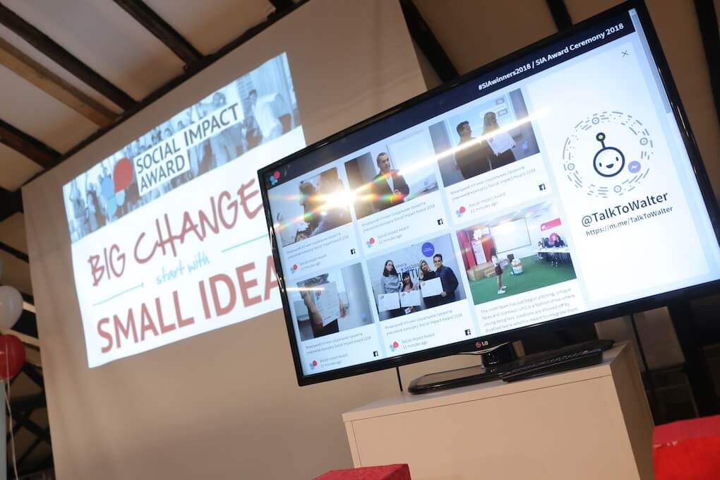 """The Social Impact Award social media wall shown on a TV screen. In the background, a projected image on a wall shows the words: """"Social Impact Award. Big changes start with small ideas."""""""