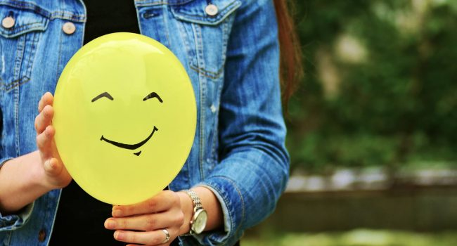 woman holding a smiley baloon
