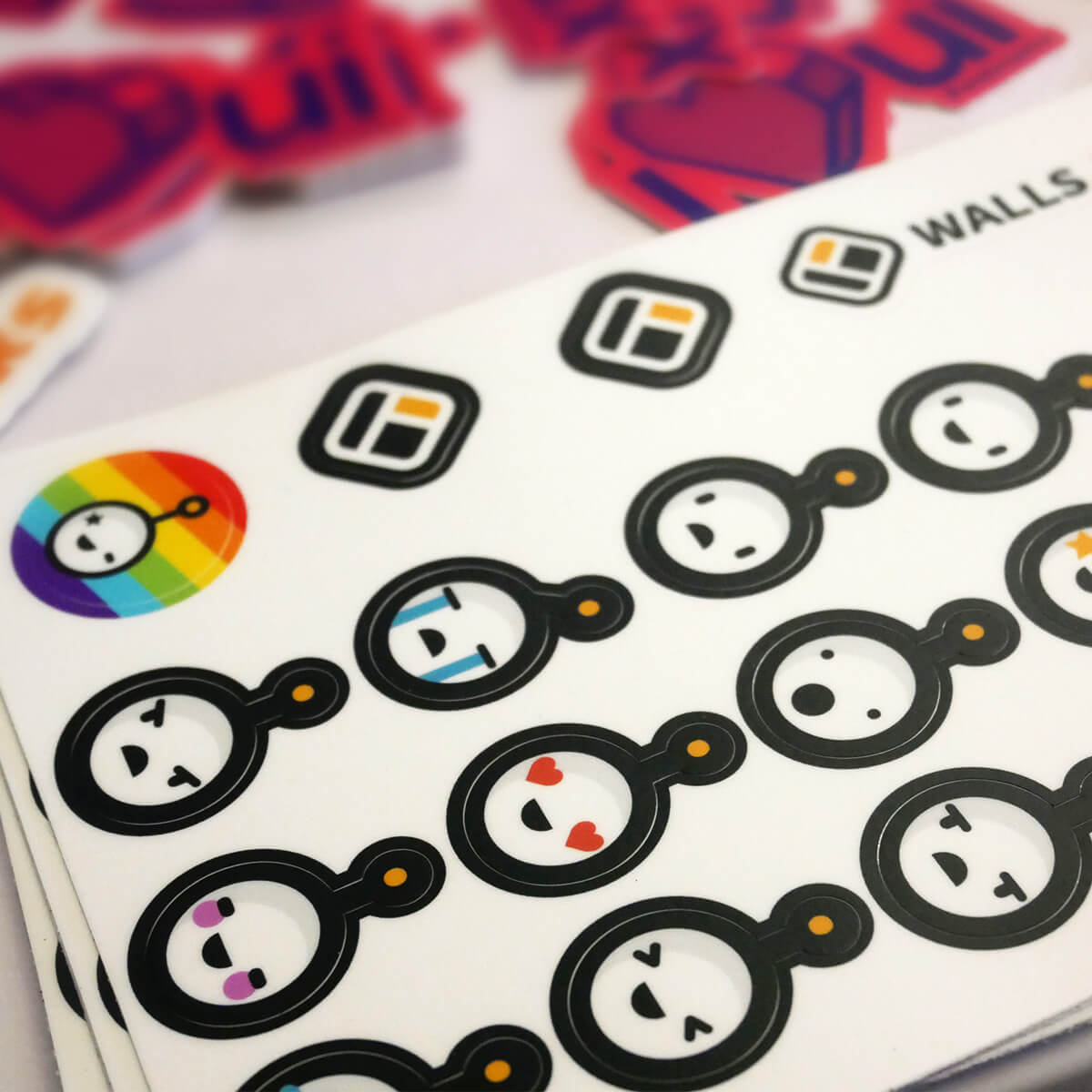 A sheet of stickers showing the Walls.io mascot robot Walter with different emoji-like expressions as well as one with a rainbow background. In the background there are some stickers of the Walls.io logo as well.