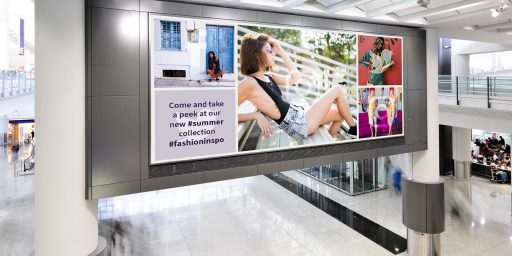 Shopping mall showing a large digital signage screen with a social wall displayed on it.