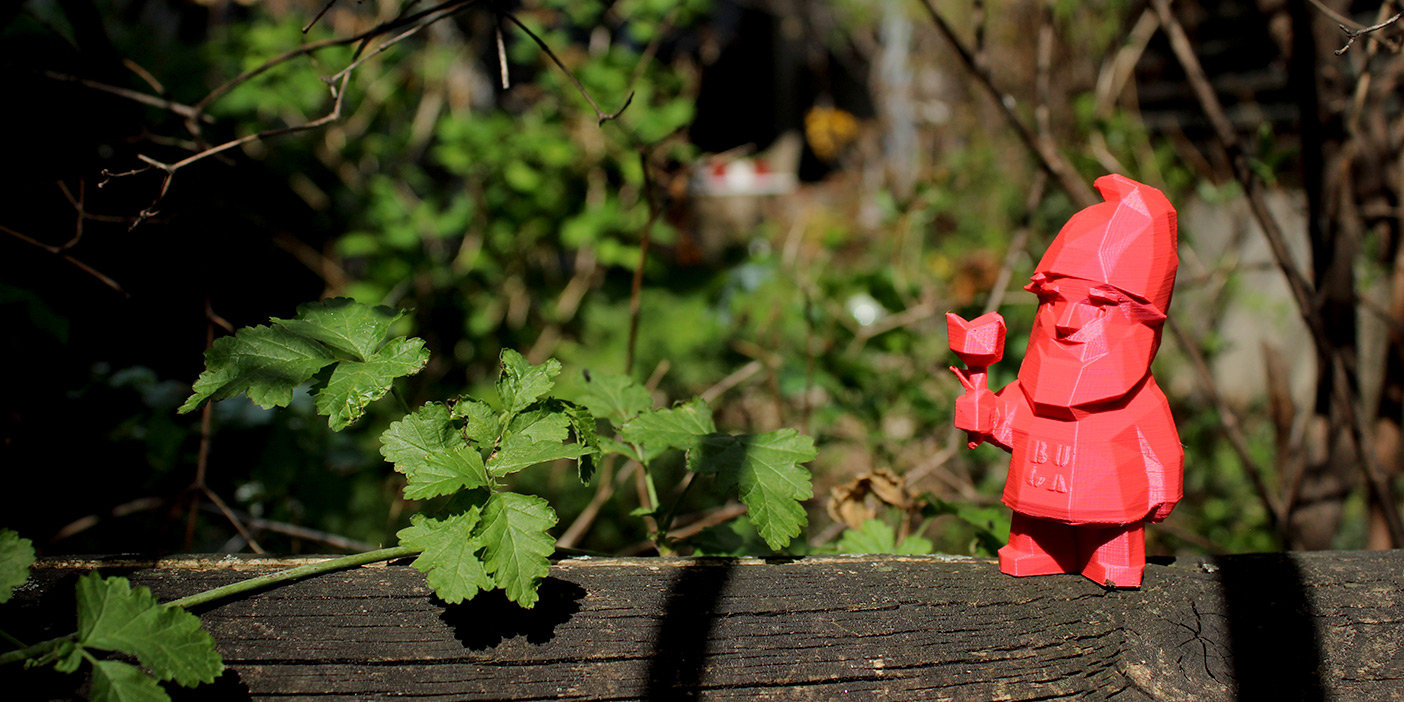 A pink, 3D-printed garden gnome holding a 3D-printed flower, placed on a wooden fence. In the background are the branches and green leaves of a tree.