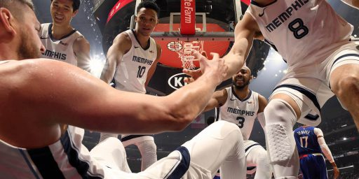 A photo shot from the view of a Grizzlies player who is sitting on the floor. Four of his teammates are standing around him helping him up.