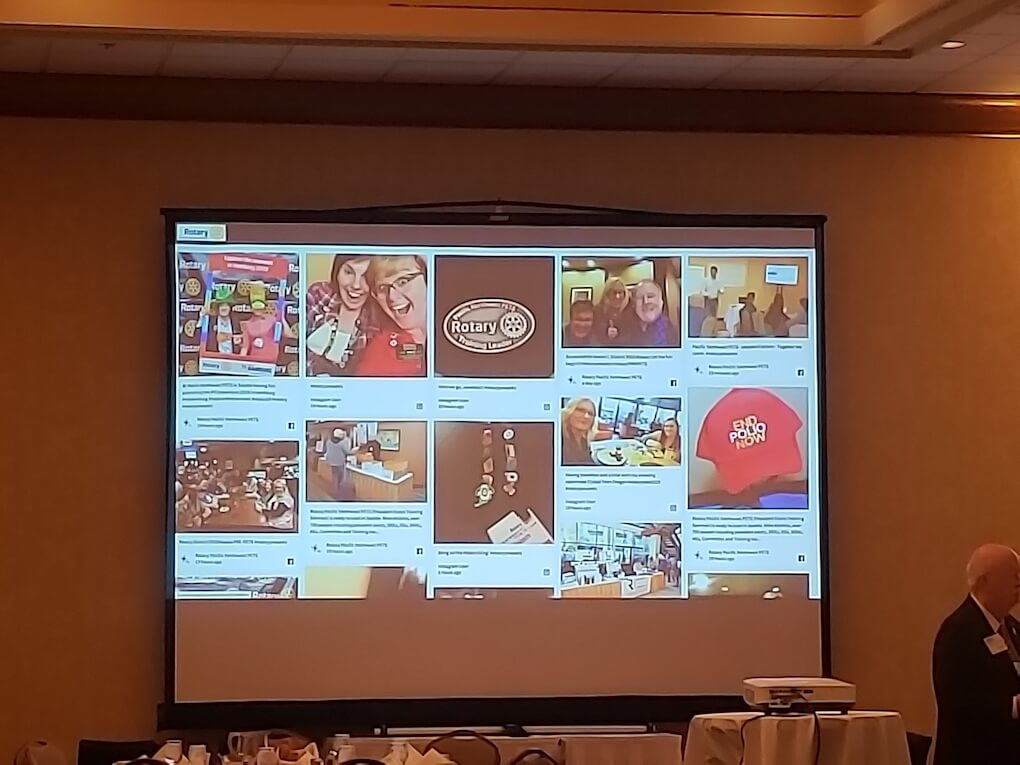 A big screen at the front of a room, showing a social media wall with posts and selfies from attendees.