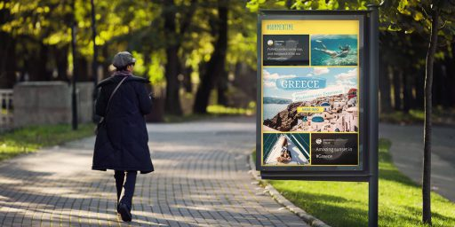 A woman walking along a path in a spring-time park, away from the camera. She is passing a big digital signage display that shows a social wall called #summertime.