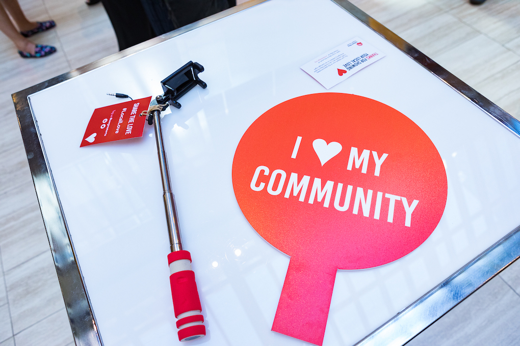 """On a square white table, props for a selfie station: a selfie stick with a tag that says """"Share the love #LocalLove"""" and a red sign reading """"I"""