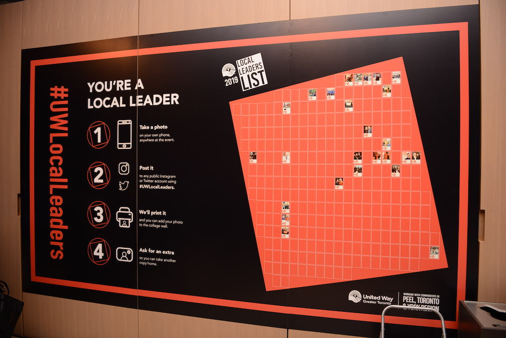 """A poster with black background, displaying a red-backgrounded grid with some printed-out selfies already pinned onto some of the squares. Above the red grid it reads """"2019 Local Leaders List"""". To the left of the grid it reads: """"You're a local leader!"""" followed by instructions for posting a selfie with the hashtag which can then be printed and pinned to the grid. The poster also boldly features the hashtag #UWLocalLeaders."""