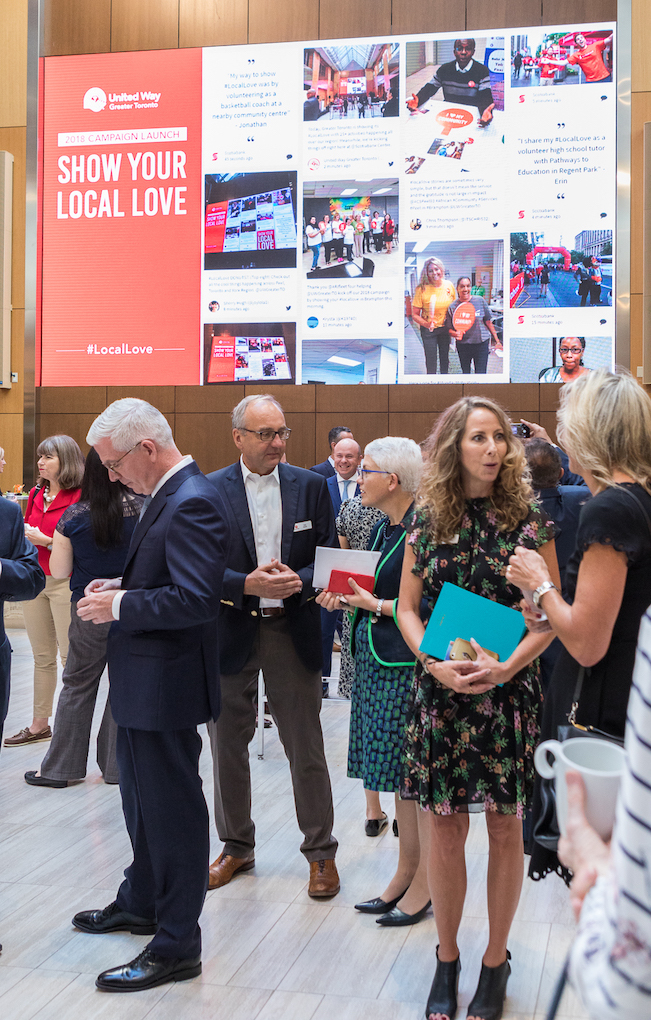 """This photo shows a loose group of people standing around at an event and talking. In the background, a social wall with the title """"Show Your Local Love"""" is projected onto a screen."""