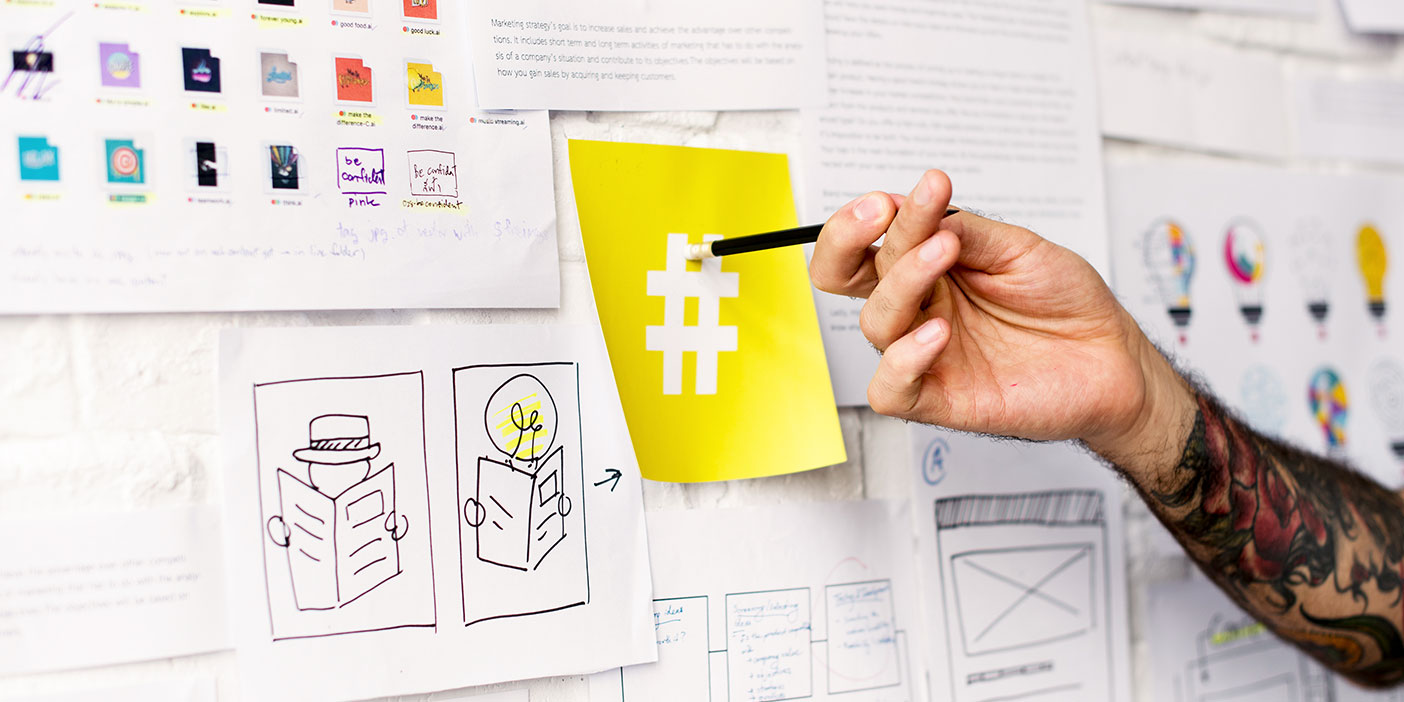 A product or website design planning board with lots of overlapping notes and drawings on individual white pieces of paper affixed to it. A person?s hand is using a black pen to point to a yellow piece of paper with a white hashtag on it.