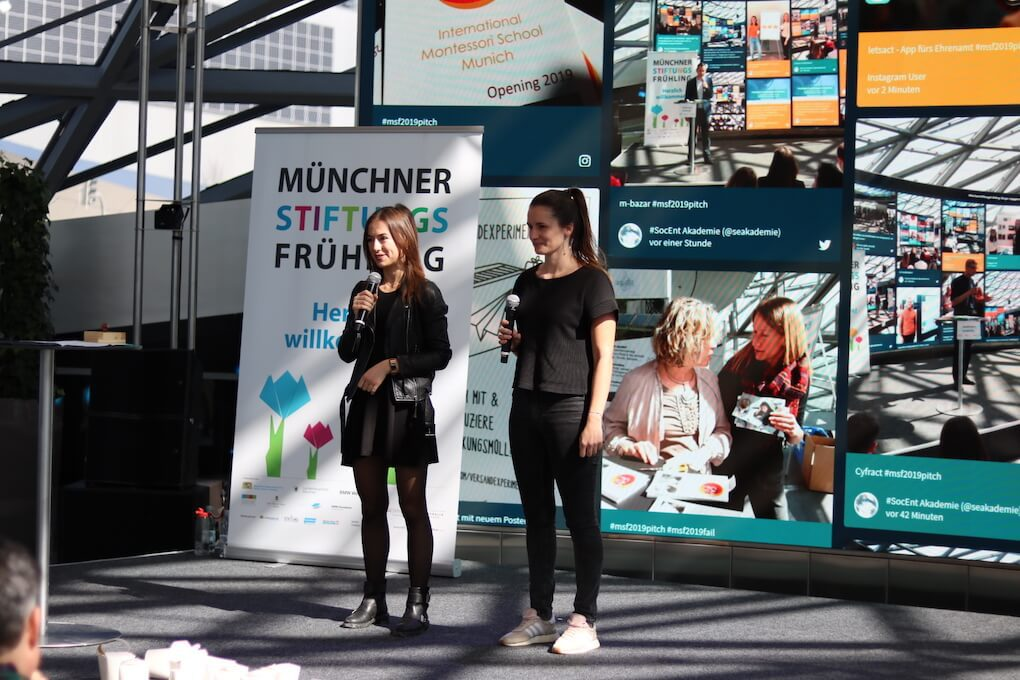 "Two people holding microphones on stage. Behind the speakers, there is a poster welcoming the audience to ""Münchner Stiftungs Frühling"". In the background, we also see a screen showing the Social Entrepreneurship Akademie social wall."