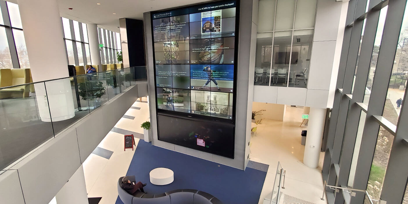 The entrance area of the Tinkham Veale University Center where a large media wall showing the social wall is set up, surrounded by seating areas. Social wall display example.