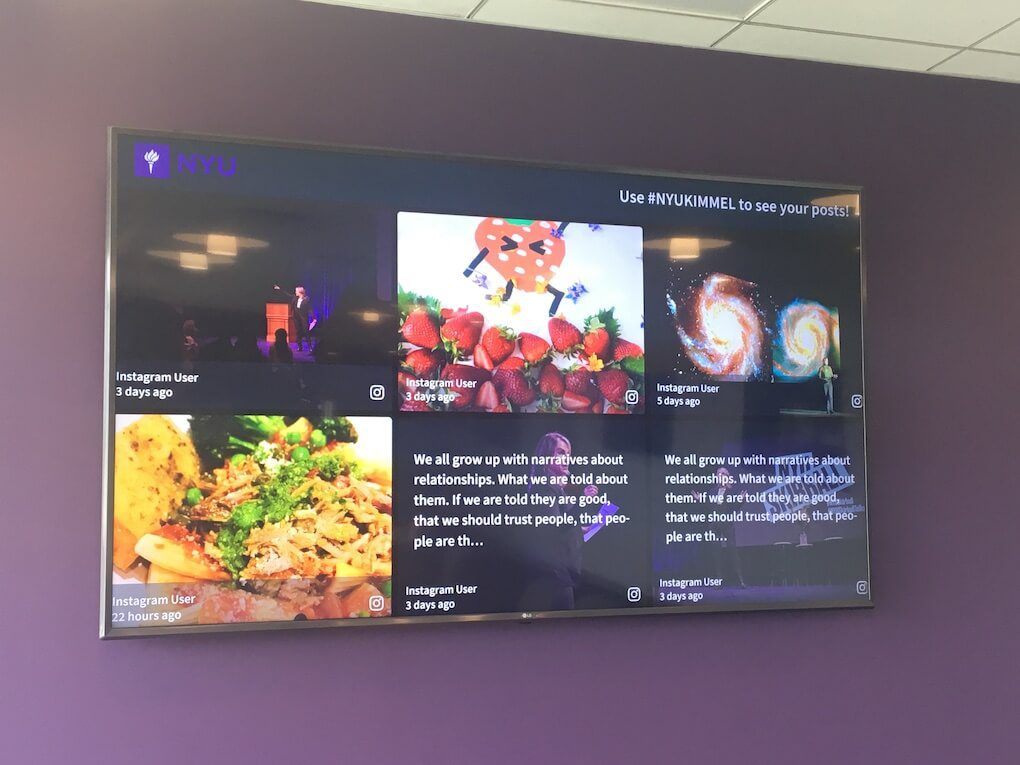 Photo of the NYU social wall on a big screen in front of a purple wall. The wall's hashtag is #NYUKIMMEL and it shows Instagram posts about various topics, from science to food to events.