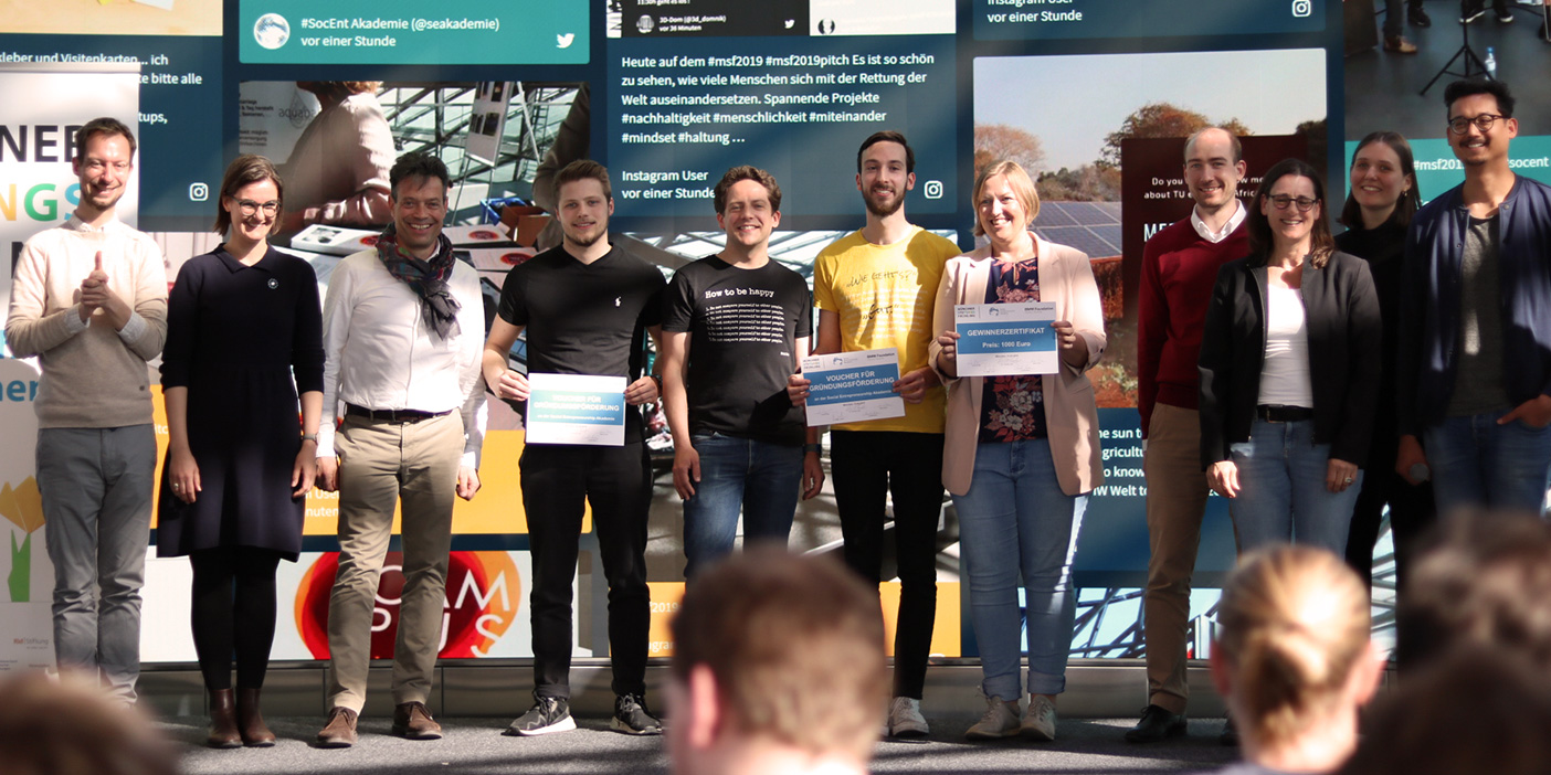 A group of people is posing for the camera on the stage in front of the social wall display. They're holding their placards showing they won at the pitching event.