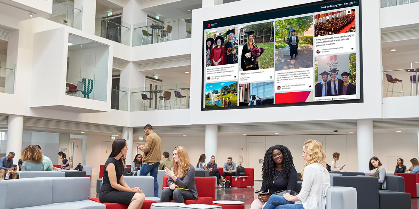 Students are sitting and chatting on sofa benches in a lobby. Behind them, a social wall is displayed on a very large screen spanning the first and part of the second floor of the gallery. The social wall shows graduation photo posts by students.