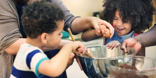 Two laughing kids are crowded around a metal mixing bowl. One is holding a wooden stirring spoon, the other one is cracking an egg into the bow. The hands of two adults are seen helping crack the egg and hold the bowl.