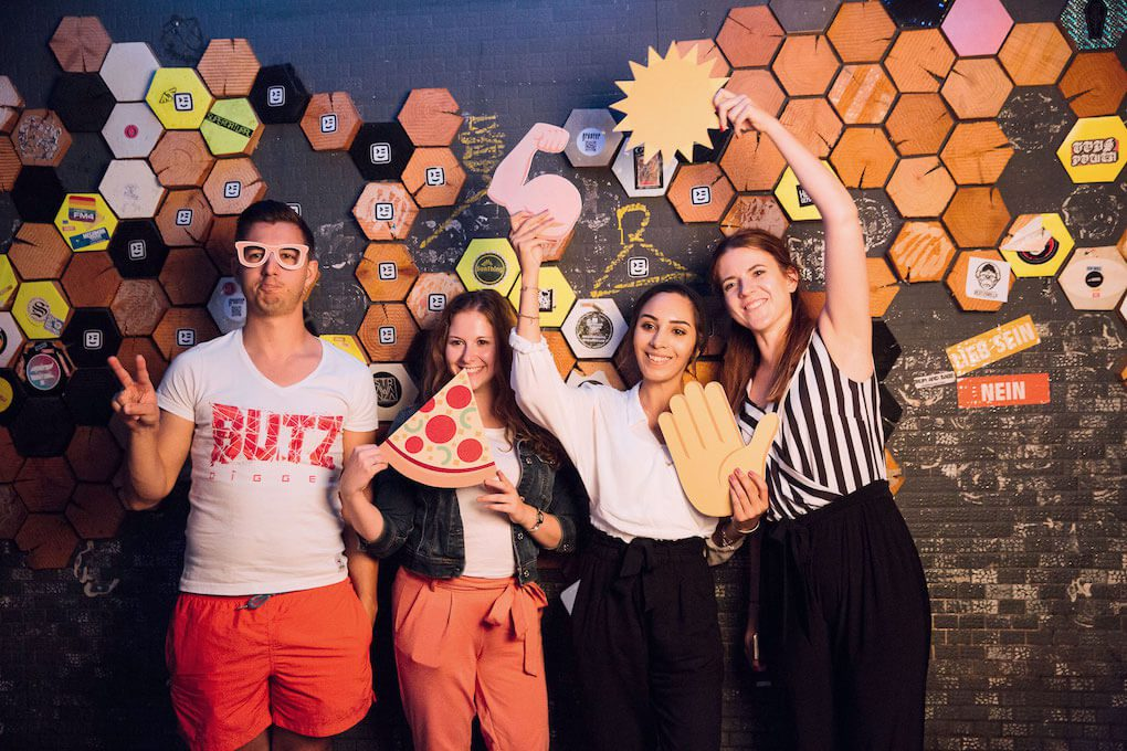 Four people in a photo booth, smiling and posing. Some of them are holding up large printouts of emoji as props: 🍕, ☀️, ✋, and 💪🏻