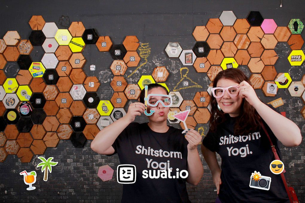 "A photo from the photo booth. Two people are posing with printed out props of glasses, snorkeling masks and drinks glasses. They're both wearing black t-shirts that read ""Shitstorm Yogi."" on the front. At the bottom edge, the image is branded with an overlay of the Swat.io logo and some summer-themed emoji."