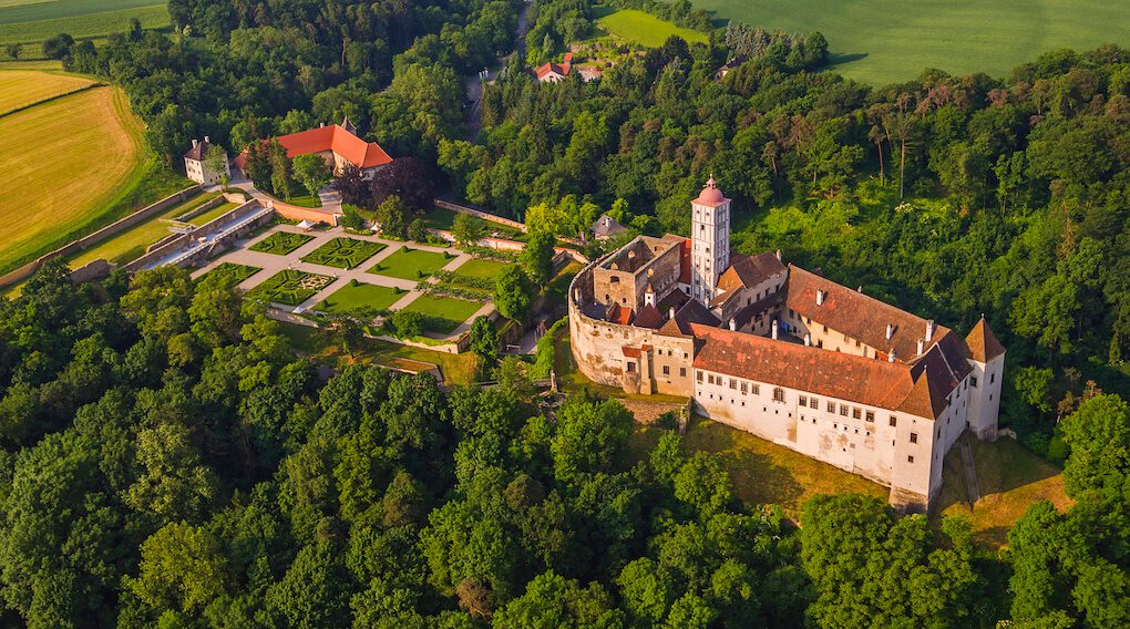 Aerial shot of Schallaburg Castle, a Renaissance castle with gardens, surrounded by woodlands.