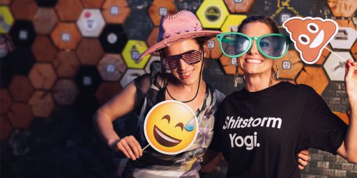 Two people smiling and posing in a photo booth. They're using props — one is wearing a pink hat and holding up the printout of a 😅emoji on a stick. The other one is wearing completely oversized sunglasses and holding up a poop emoji printed and mounted on a stick