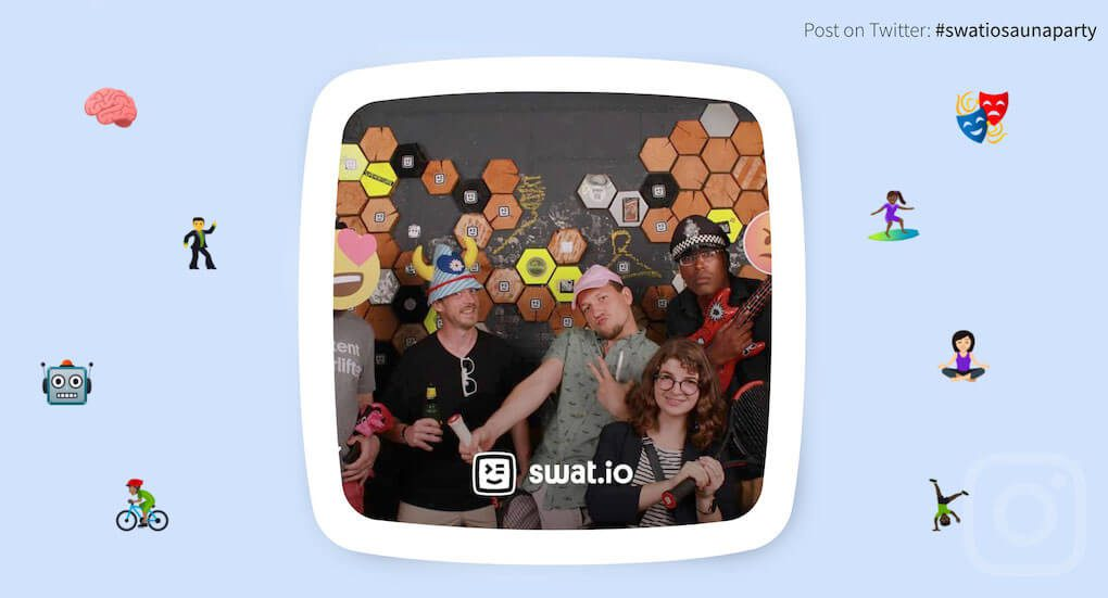 Screenshot of the Swat.io social wall using the Kiosk theme. The wall is designed with various emoji icons on a light blue background. In the middle of the page, a photo from the social wall is shown with a white border. In the photo we see six people having fun with various props, such as funny hats and emoji faces, in the photo booth.