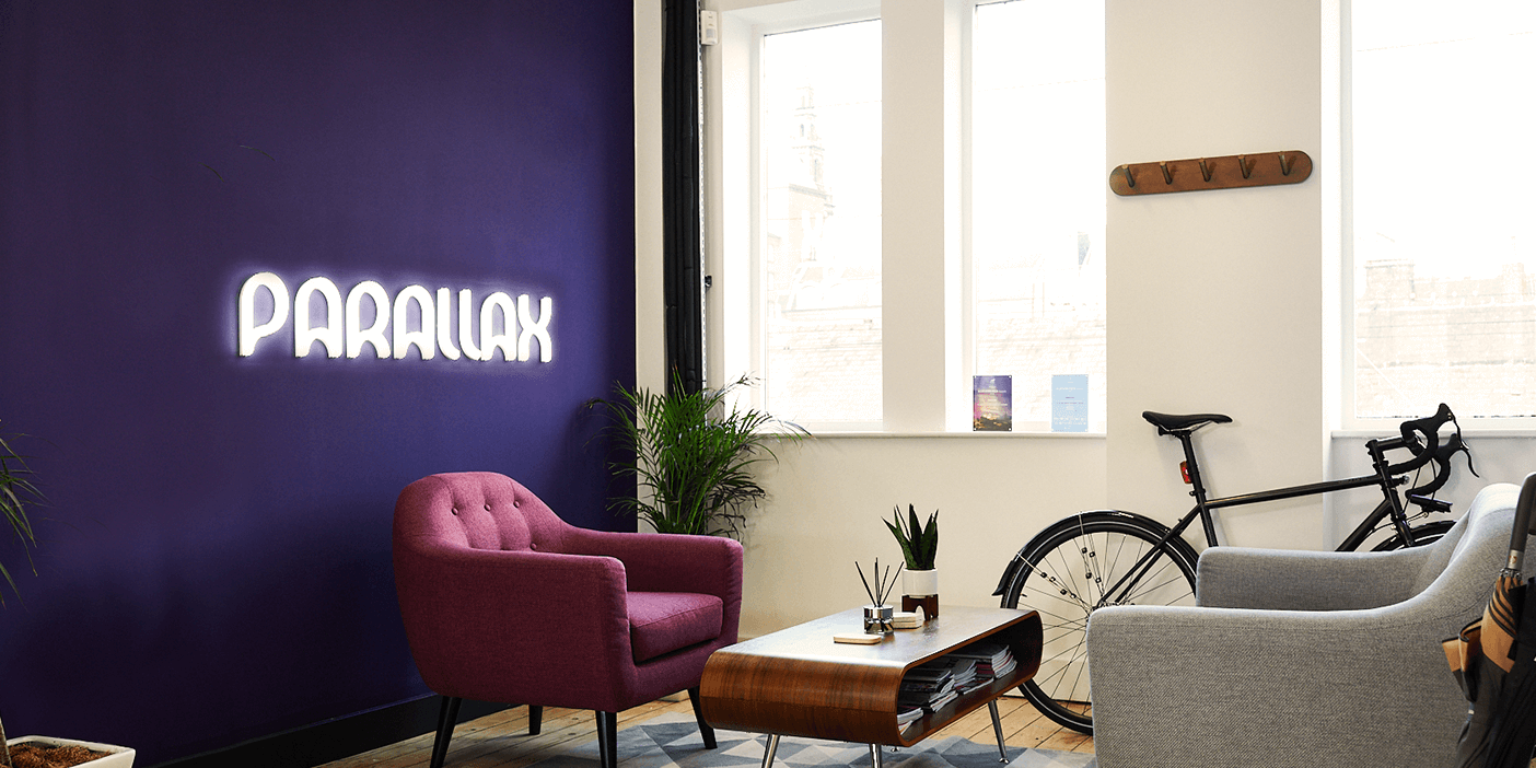 "A comfortable-looking maroon armchair in front of a purple wall which bears the word ""Parallax"" in white neon letters. Across from the armchair, there's a grey sofa. Between them, a coffee table with a plant and a few pens upon it. Under the sitting area is a geometric rug. Against the white wall with windows behind the sitting arrangement leans a bicycle. In the foreground, a potted plant on the left and an umbrella stand with one umbrella on the right frame the picture."