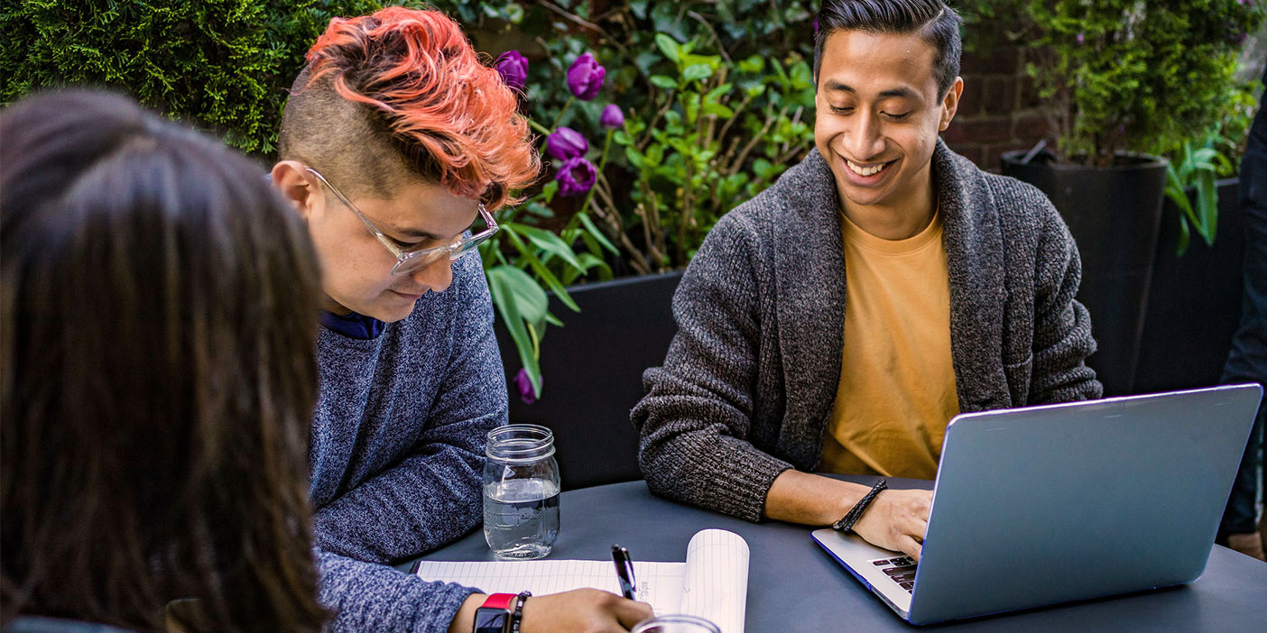 Three people sitting around a table, working on something together. They are smiling. One of them has a laptop open, another one is writing on a notepad. The third person has their back to the camera.