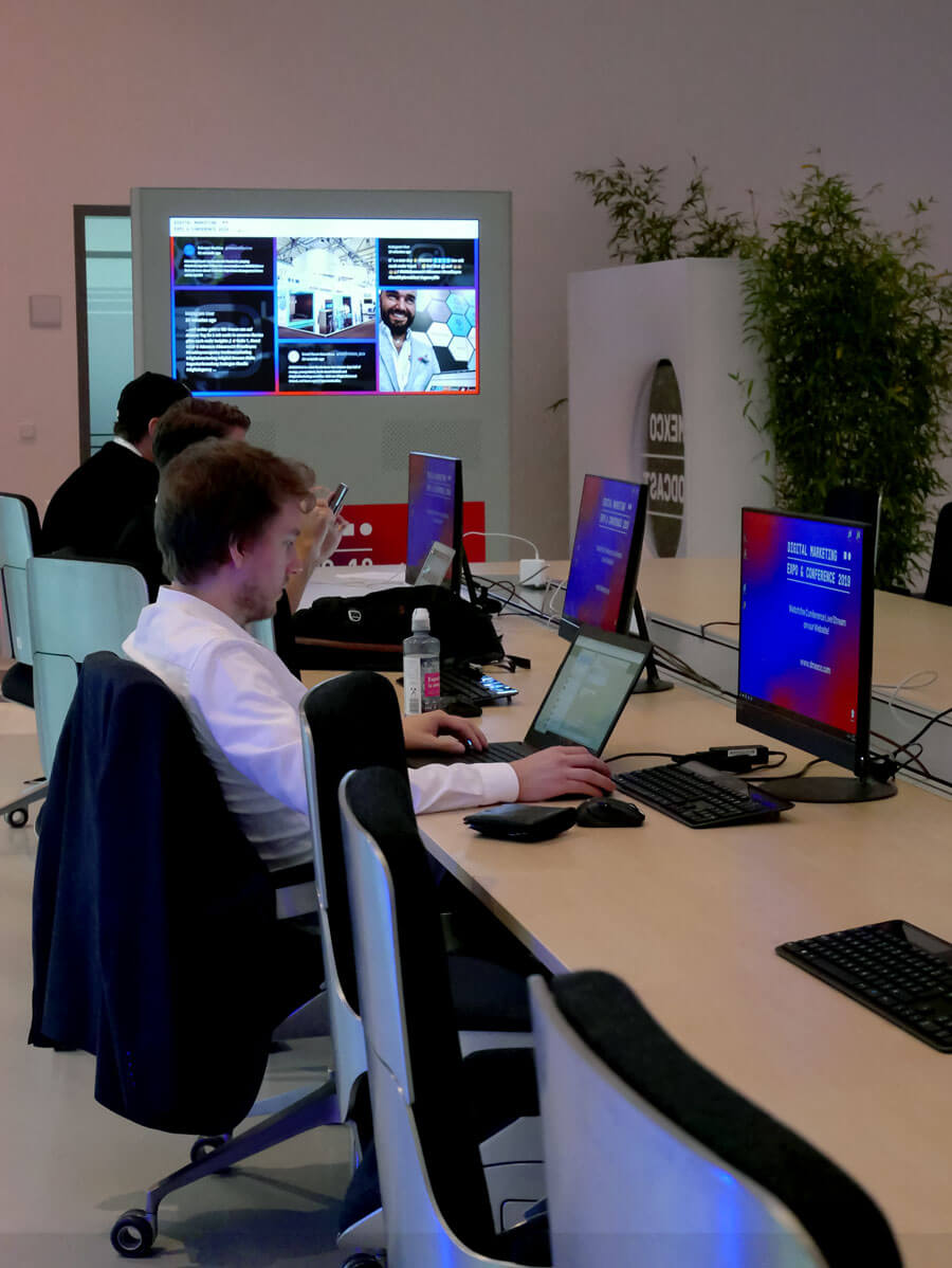 A long table with work stations on the left-hand side. Three people are sitting on the left side, working on their laptops. At the far end of the room, a screen is set up with the DMEXCO social media wall. It's positioned so that the people working at the table can easily look at it by turning their heads to the left a little.