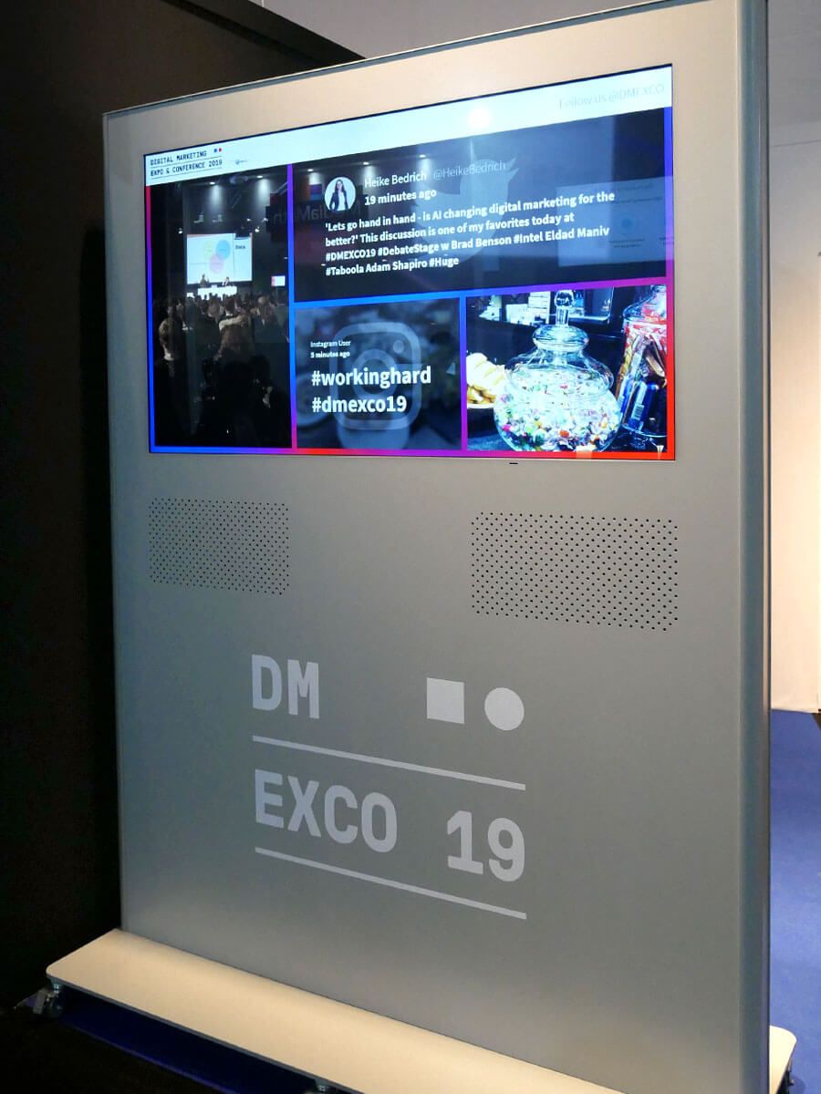 A DMEXCO 19 branded human-height display with an integrated screen is showing the DMESCO social media wall using the Bricks theme. Various posts are visible, showing photos taken at the event. One of the posts uses the hashtags #workinghard and #dmexco19.
