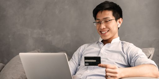 A smiling person sitting on a sofa with a laptop on their lap and holding a credit card in their hand.