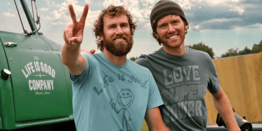 "The two founders of Life is Good, standing next to each other, smiling. The one on the left has a beard and is making a peace sign with his right hand, the one on the right has a beanie on his head. Both have red hair and are wearing Life is Good t-shirts with positive messages printed on them. In the background there's a green truck with a ""Life is Good Company"" decal on it."